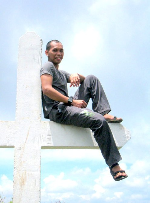 Sitting on the Famous Cross of a Mountain's Peak